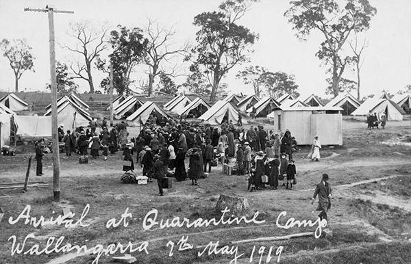 People arrive at the quarantine camp in Wallangarra during the influenza epidemic of 1919. The camp consists of tents and corrugated iron buildings, surrounded by bushland. People are waiting to be registered and admitted to the camp. They have their suitcases and other belongings with them.