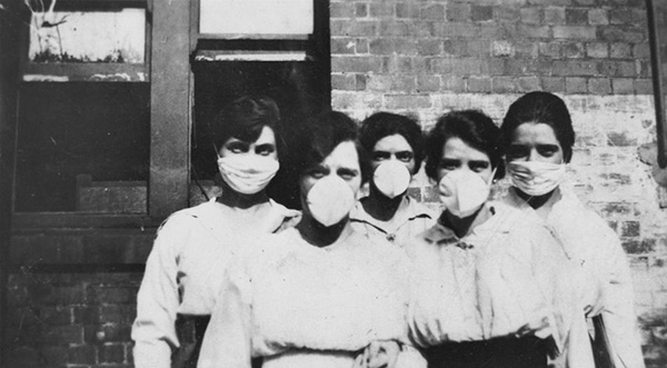 Five women are standing in front of a brick building, possibly a hospital, wearing surgical masks during the Spanish 'Flu outbreak in Brisbane, 1919.